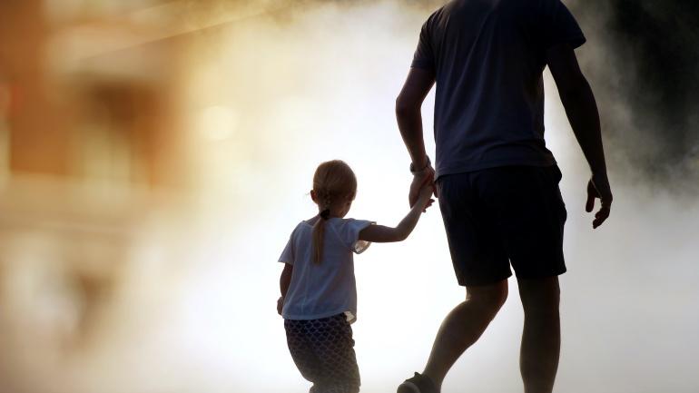 barn som holder far i hpnden på vei ut fra en brann