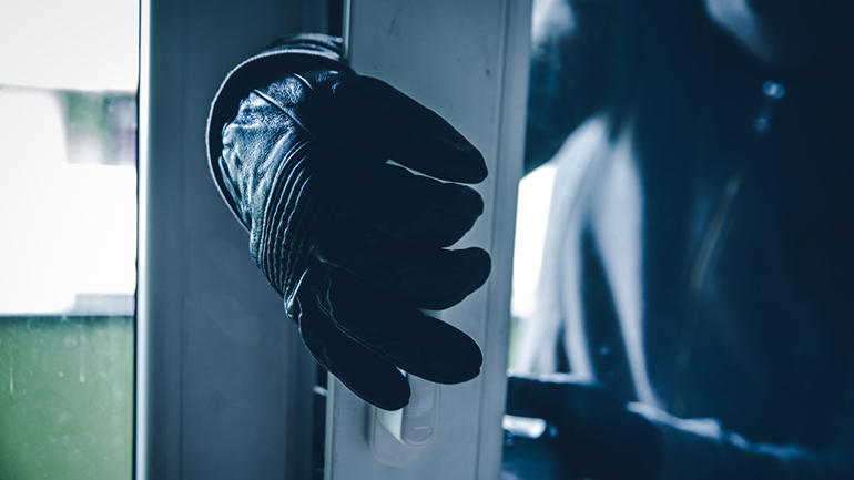 En tyv som prøver å lirke seg inn verandadøra